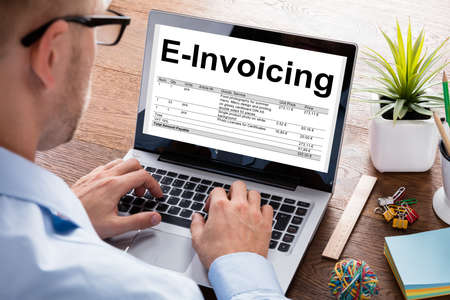 Cropped image of businessman preparing e-invoicing bill on laptop at desk in office Archivio Fotografico