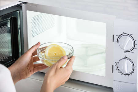 Close-up Of Woman Putting Bowl Of Slice Lemon In Microwave Oven Stok Fotoğraf - 85014132
