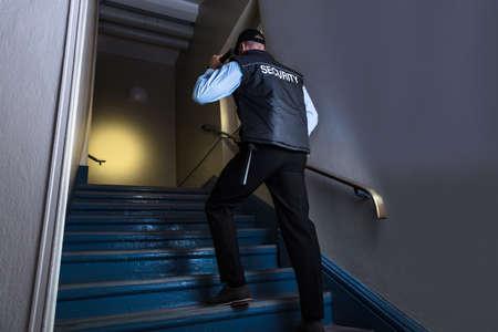 Hintere Ansicht eines männlichen Sicherheitsbeamten mit Taschenlampe