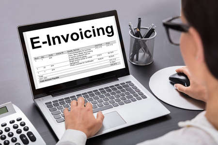 Cropped image of businesswoman preparing e-invoicing bill on laptop at desk in office Stock Photo