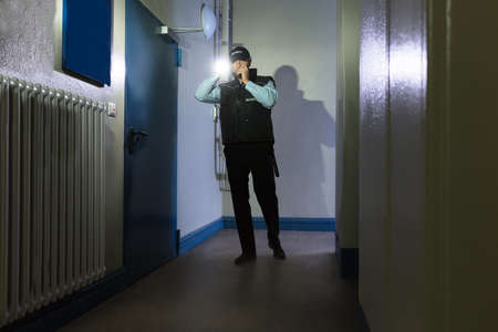 light duty: Male Security Guard With Flashlight Standing In Corridor Of The Building