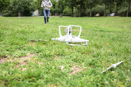 White Quadrocopter Fallen On Grass With Operator Running In The Background