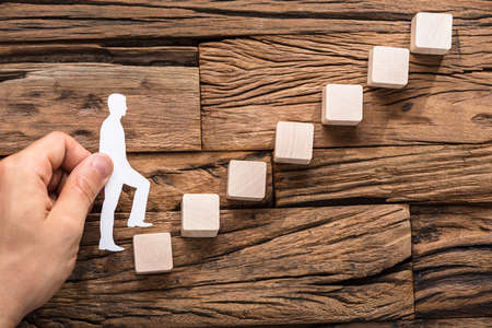 Close-up Of Hand Stepping The Paper Cut Out Figure On Increasing Arranged Blocks Stock Photo - 84988305