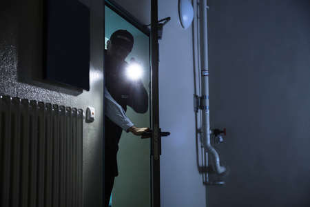 light duty: Male Security Guard Searching With Flashlight At Industry