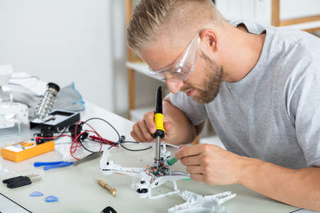 Man In Protective Glasses Fixing The Quadrocopter Drone On Table With Different Tools