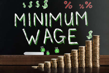 Minimum Wage At Blackboard Behind Stacked Coins Banco de Imagens