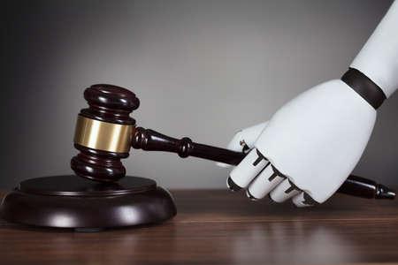 Close-up Of Robots Hand Hitting Gavel At Wooden Desk
