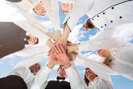 Low Angle View Of Multiracial Restaurant Staff In Uniform Stacking Hands Stock Photo