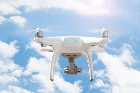 Low angle view of drone flying against cloudy sky Stock Photo