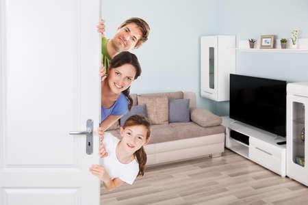Portrait de famille heureuse faisant un aperçu de la porte dans le salon