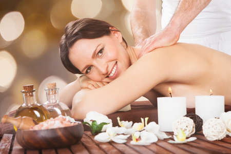 Close-up Of A Happy Woman Receiving Shoulder Massage In Spa Stock Photo