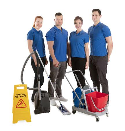 Retrato de felices conserjes con equipos de limpieza contra el fondo blanco