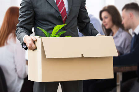 Mid Section View Of A Businessperson Holding Belongings In Cardboard Box At Workplace