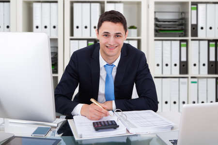 Portrait Of A Happy Young Accountant Calculating Invoice Stock Photo
