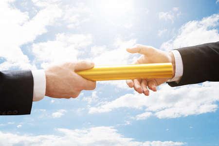 Persoon die Gouden Relay Baton doorgaat naar een andere persoon tegen bewolkte lucht Stockfoto