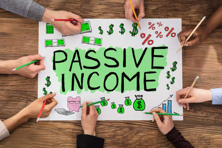 Group Of People Drawing Passive Income Concept In Notepad