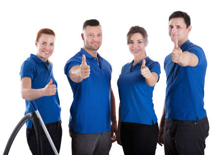 Portrait Of Happy Janitors Showing Thumb Up Sign Against White Background Archivio Fotografico