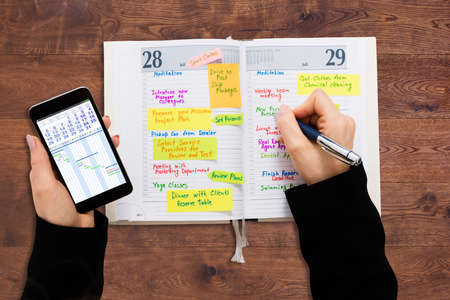 High Angle View Of A Businessperson With Mobile Phone Writing Schedule In Diary Stock Photo