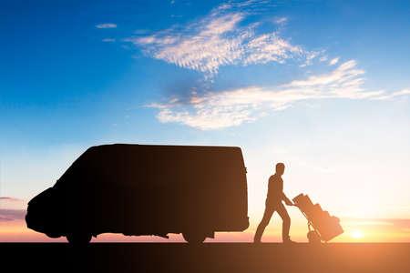 silhouette de la livraison avec des boîtes en carton sur chariot près de la remorque au coucher du soleil