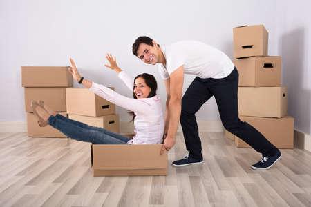 행복 한 젊은 남자 집에서 골 판지 상자에 앉아 여자를 밀고