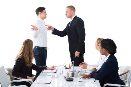 Boss Shouting On Male Executive In Business Meeting