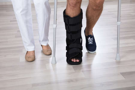 Low Section View Of Physiotherapist And Injured Persons Leg Wearing Walking Brace Imagens