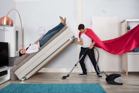 Young Man Wearing Red Cape Cleaning Under The Couch With Vacuum Cleaner Foto de archivo