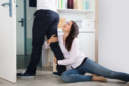 Woman Desperately Clinging To The Leg Of A Man At Home