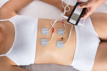 High Angle View Of A Therapist Giving Electrodes Therapy On Womans Stomach