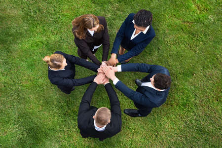 Elevated View Of Businesspeople Standing On Green Grass Stacking Their Hands