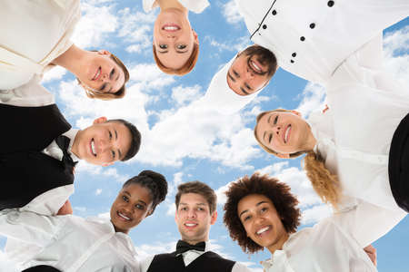 Smiling Restaurant Staff Forming Huddle Against Cloudy Sky Stok Fotoğraf