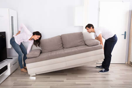 work life balance: Young Woman Having Backpain While Lifting The Sofa With Her Husband Stock Photo