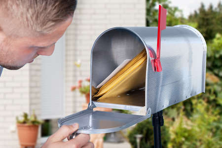 Close-up Of A Man Looking Inside The Silver Mailbox