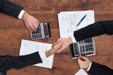 trusted: Elevated View Of Two Businesspeople Shaking Hands With Invoice Over Wooden Desk
