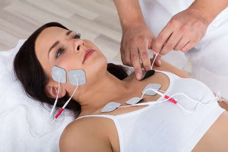 Close-up Of A Therapists Hand Placing Electrodes On Young Womans Chest