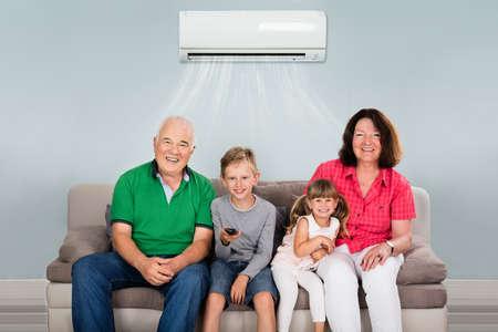 Gelukkige Multigeneratiefamilie met Twee Jonge geitjes die op Televisie onder Airconditioning thuis letten Stockfoto