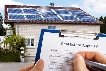 Primer plano de formulario de evaluación de bienes raíces de relleno de mano de una persona en frente de la casa Foto de archivo
