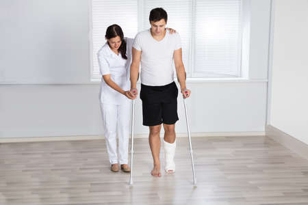 Physiotherapist Assisting Injured Young Male Patient To Walk With Crutches In Clinic