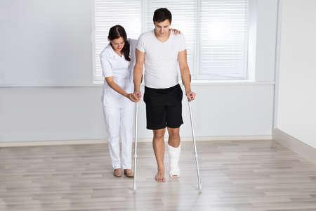 Physiothérapeute aidant blessé jeune patient masculin à marcher avec des béquilles en clinique Banque d'images