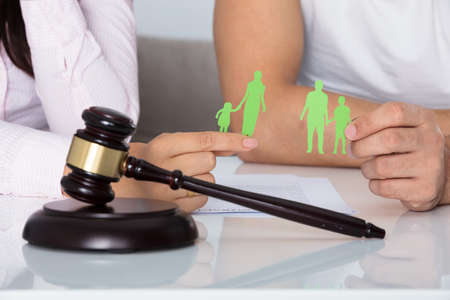 Man And Woman Holding Family Figure Cut Out Behind Gavel In Courtroom