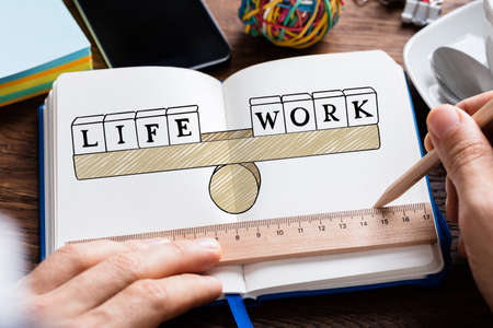 work life balance: Close-up Of Persons Hand Drawing Life Work Balancing Concept In Book Stock Photo