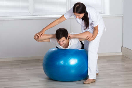 Young Female Physiotherapist Assisting Man While Doing Exercise On Fitness Ball Foto de archivo
