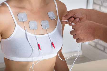 Close-up Of A Therapists Hand Giving Electrodes Therapy To Woman