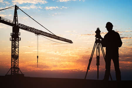 Silueta de un topógrafo de pie con el equipo cerca de la grúa en el sitio de construcción durante la puesta de sol