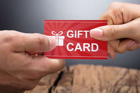 Close-up Photo Of Hands Exchanging Gift Card