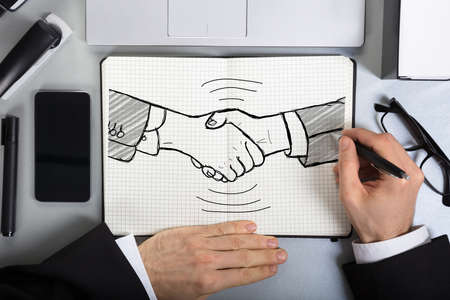 trusted: Close-up Of A Business Person Drawing Handshake Concept In Grid Book On Desk