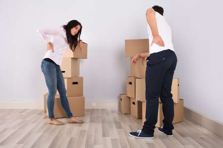Young Couple Have Backpain While Moving The Boxes In Apartment