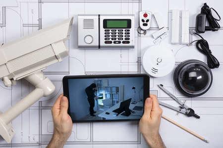Person, die Büroüberwachungskamera auf Handy mit Sicherheits-Ausrüstungen auf Plandokument betrachtet Standard-Bild