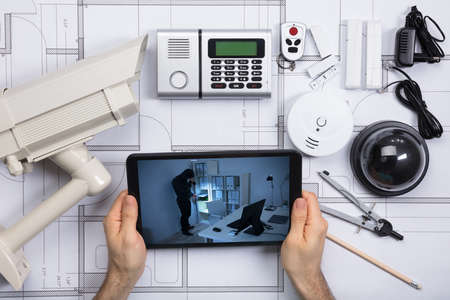 Person Looking At Office Security Camera On Mobile Phone With Security Equipments On Blueprint Document Stockfoto