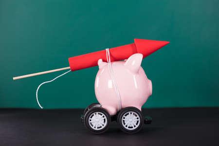 Red Rocket Firework Tied Up With Piggy Bank Over Black Background Reklamní fotografie